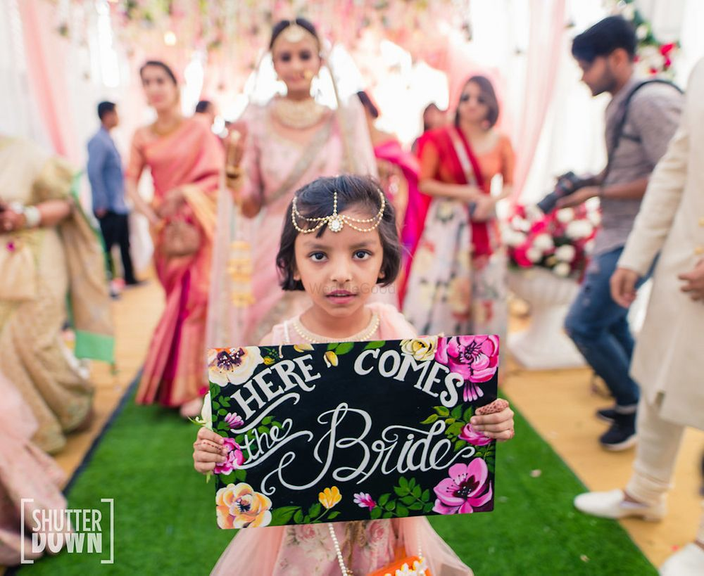 Photo of Cute bridal entry with niece holding board