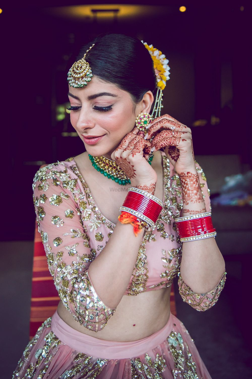 Photo of A bride wears her jewellery as she gets ready for he big day.