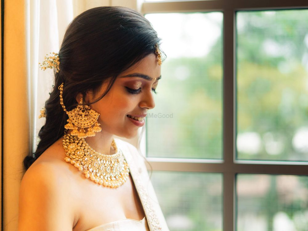 Photo of A bride flaunting her gold choker and waterfall earrings with multiple jhumkis