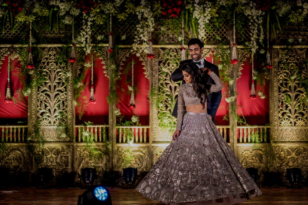 Photo of A couple in coordinated outfits dance at their sangeet ceremony