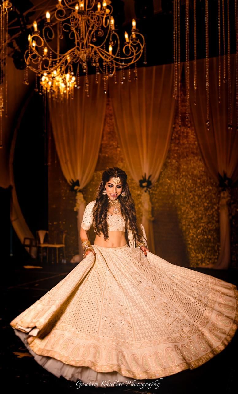 Photo of Twirling bride shot with Ivory and gold lehenga