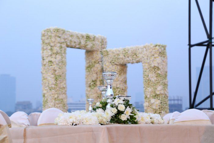 Photo of elegant white centerpieces with white roses and candles