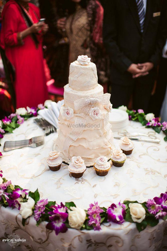 Photo of White wedding cake with cupcakes