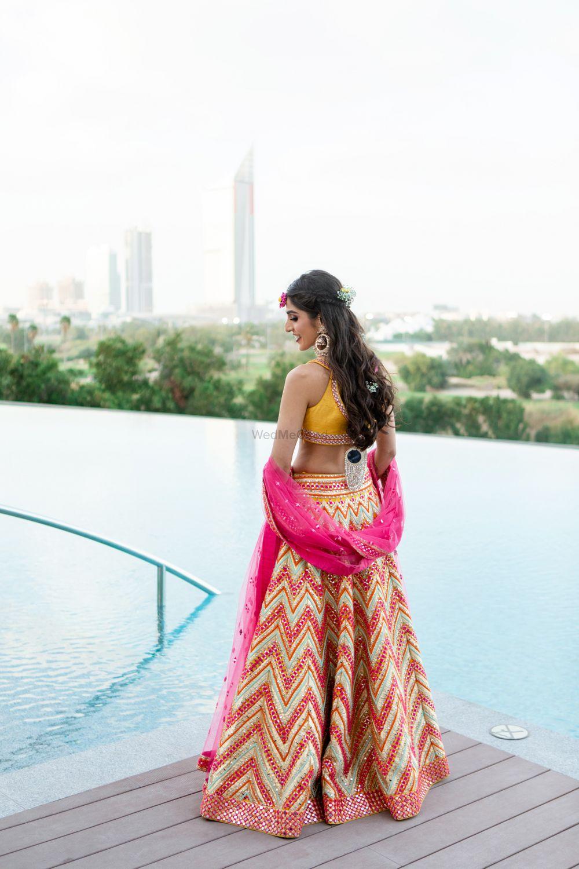 Photo of Bride wearing chevron print lehenga with mirror work.