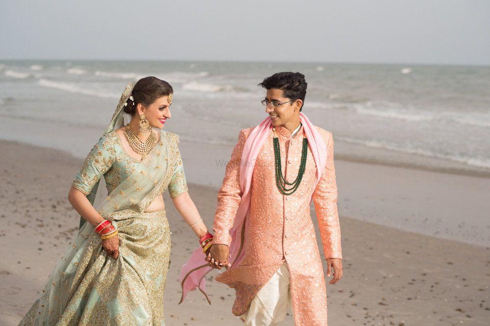 Photo of Couple portrait on the beach with offbeat sabya lehenga