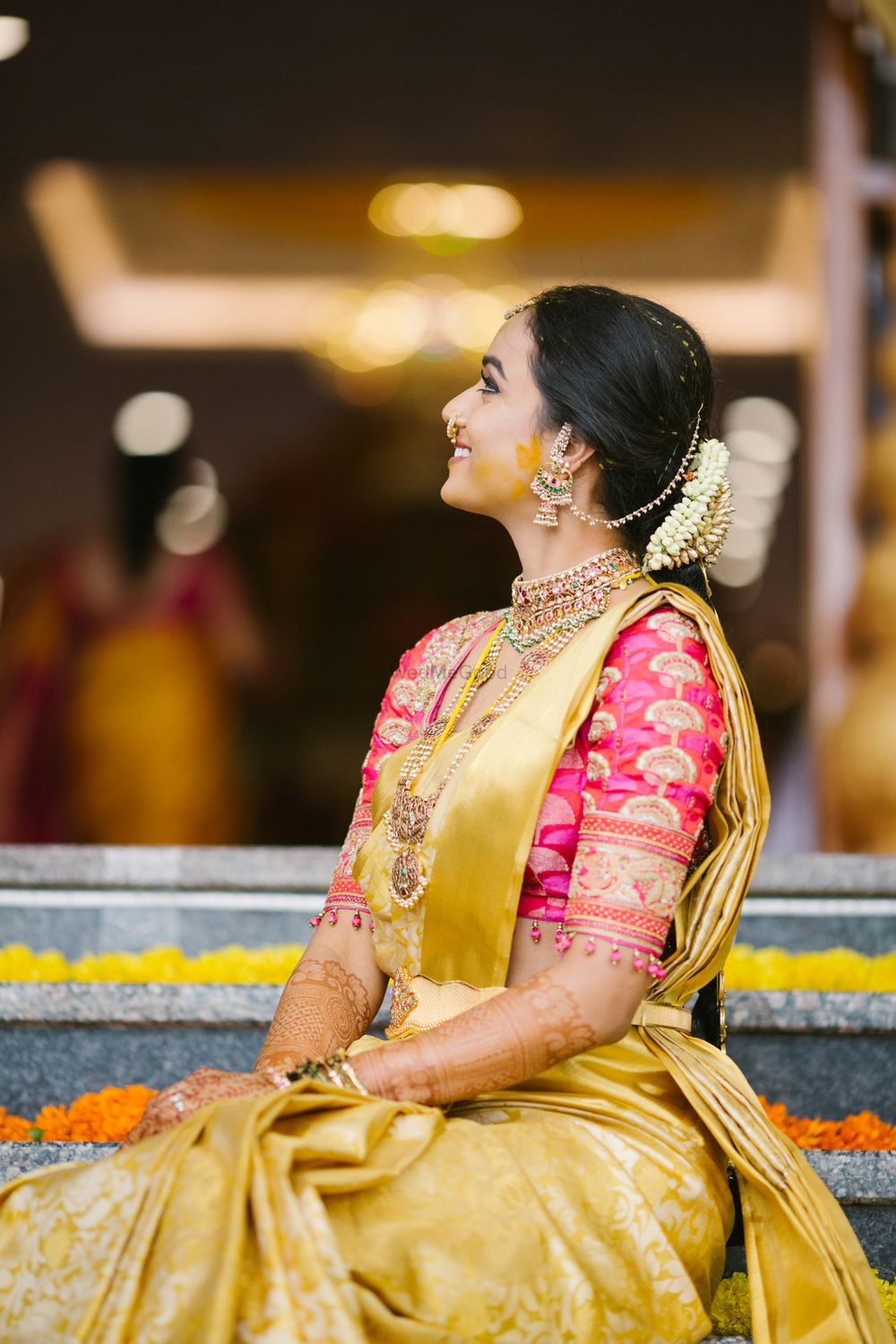 Photo of A happy bridal shot in yellow and gold saree.
