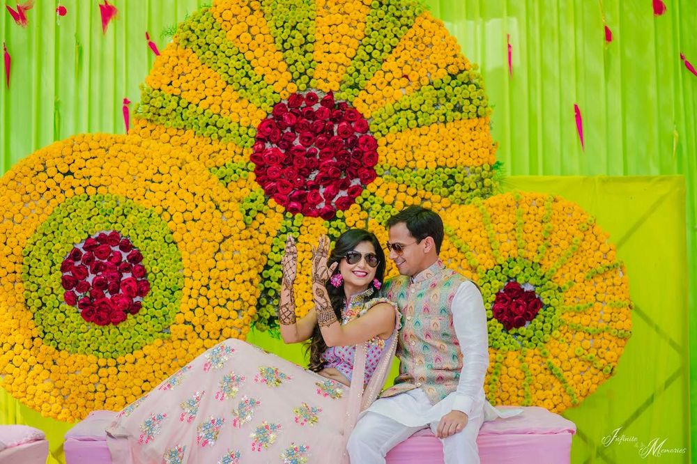 Photo of A bride and groom pose during their mehendi ceremony