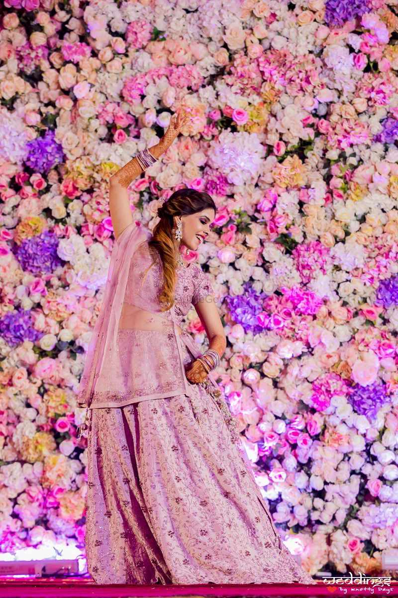 Photo of Bride dancing against a floral backdrop on stage