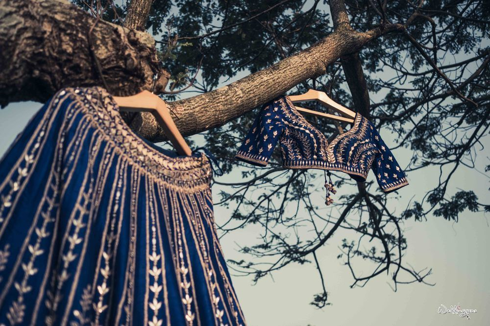 Photo of Dark blue lehenga and blouse on hanger hanging on tree