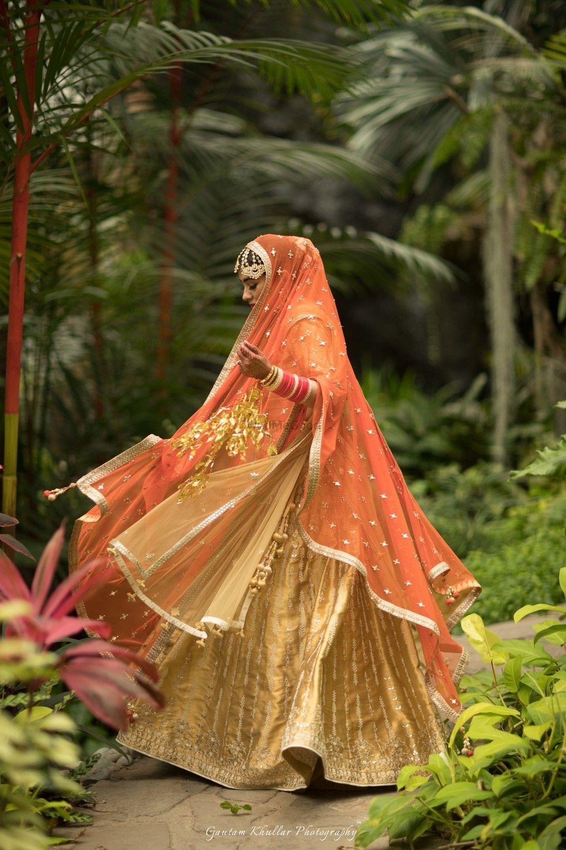 Photo of Gold lehenga with orange dupatta twirling bride
