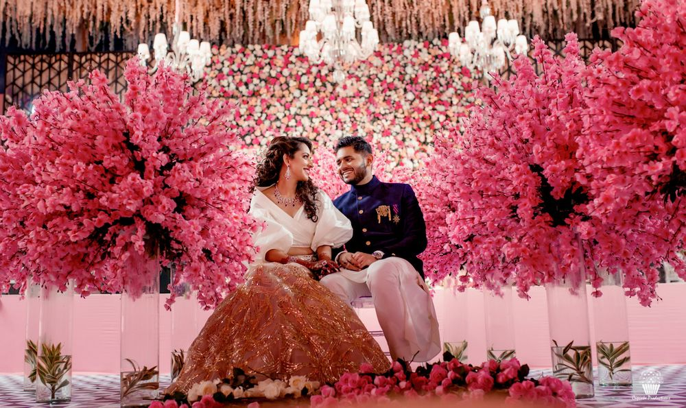 Photo of Couple pose amidst floral stage decor