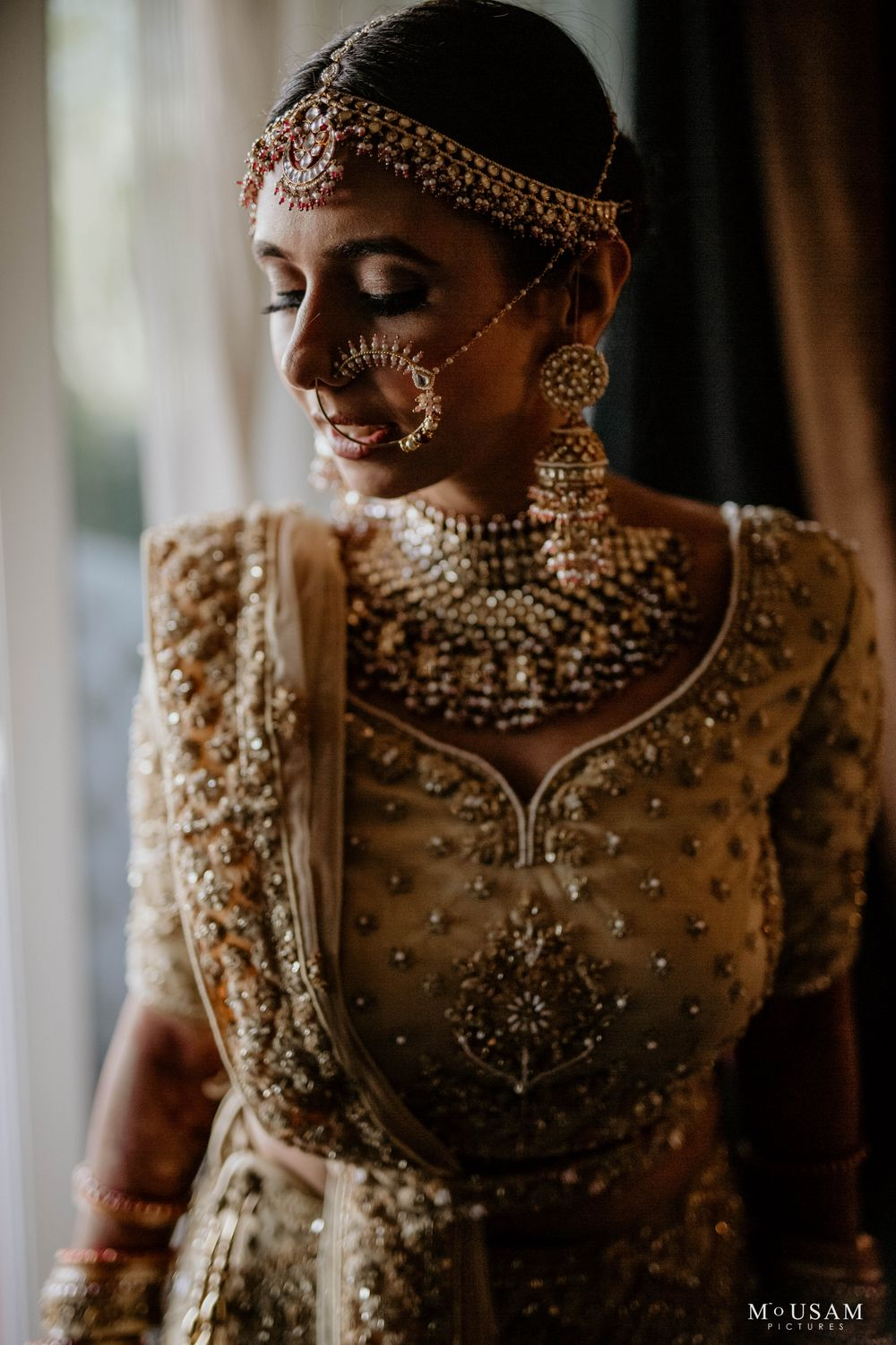 Photo of bridal close up shot with gold jewellery and lehenga