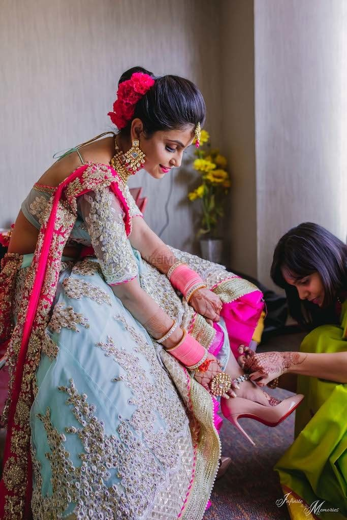Photo of A bridesmaid helps the bride with her shoes.