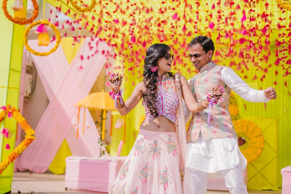 Photo of A coordinated bride and groom dance on their mehendi function.