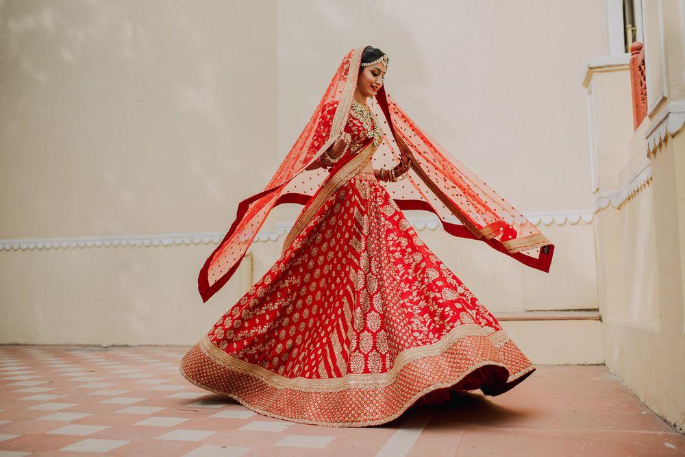 Photo of Red and gold sabyasachi bridal lehenga twirling