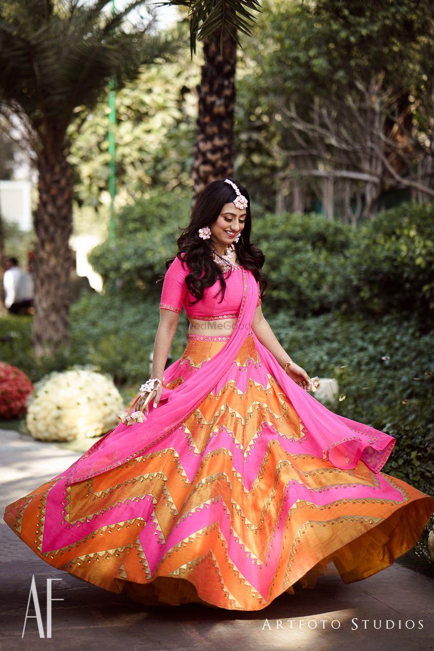 Photo of Bride twirling in bright pink and orange mehendi lehenga