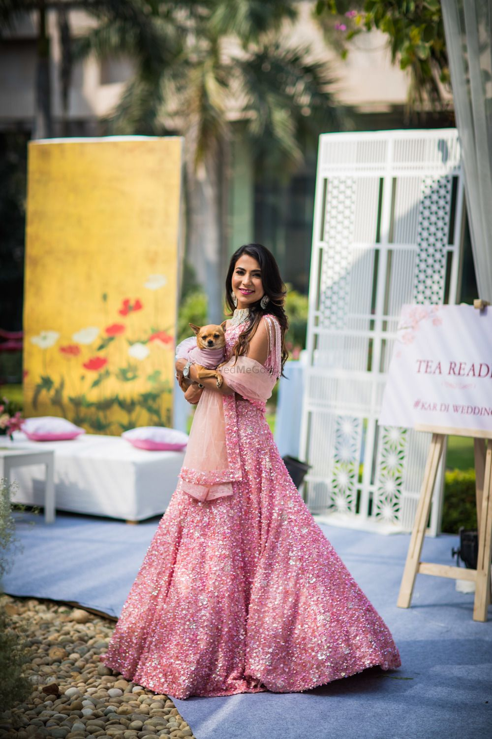 Photo of Bride in pink engagement outfit with dog
