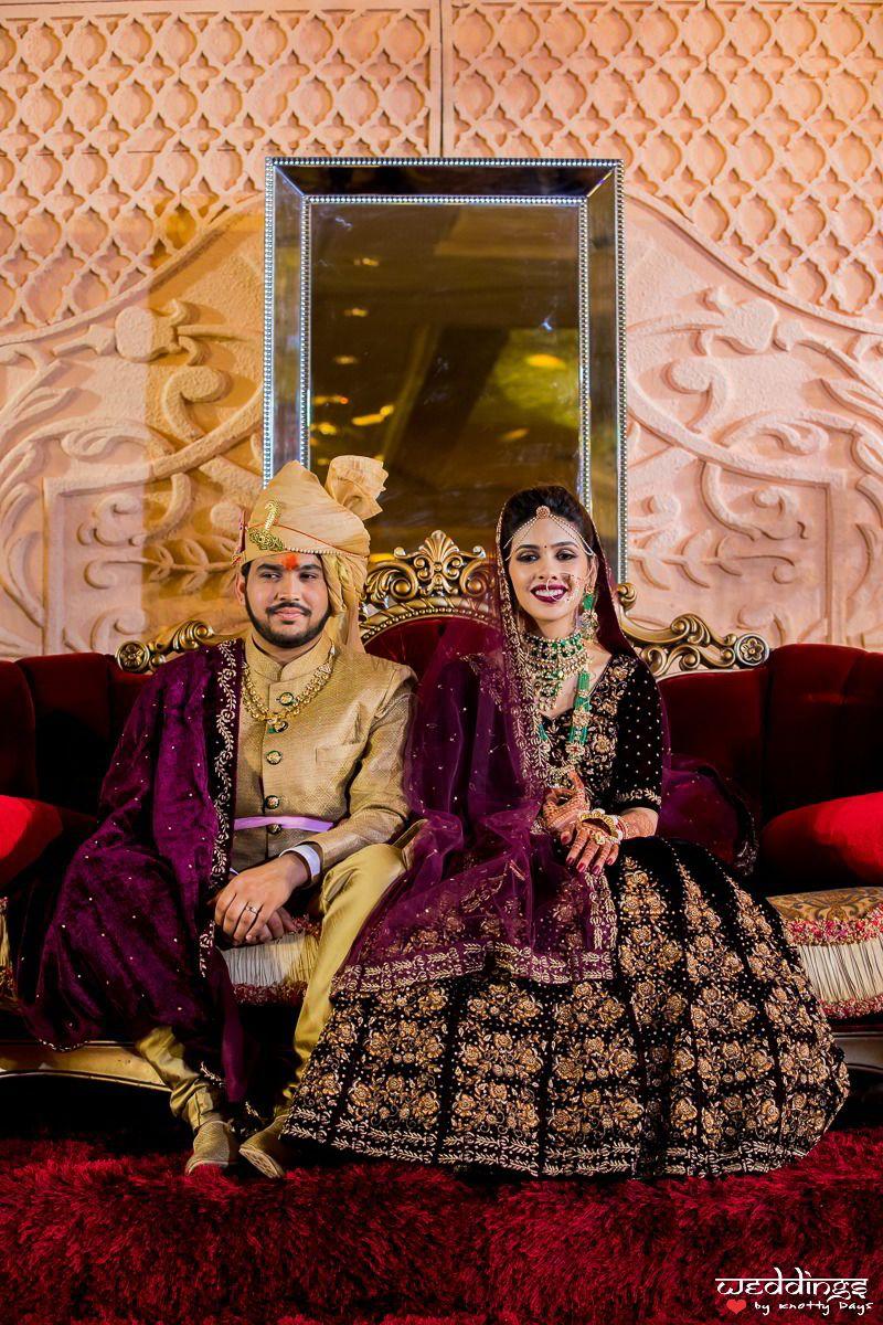Photo of Matching bride and groom in purple velvet lehenga