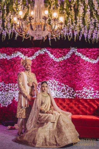 Photo of Coordinated bride and groom in gold outfits