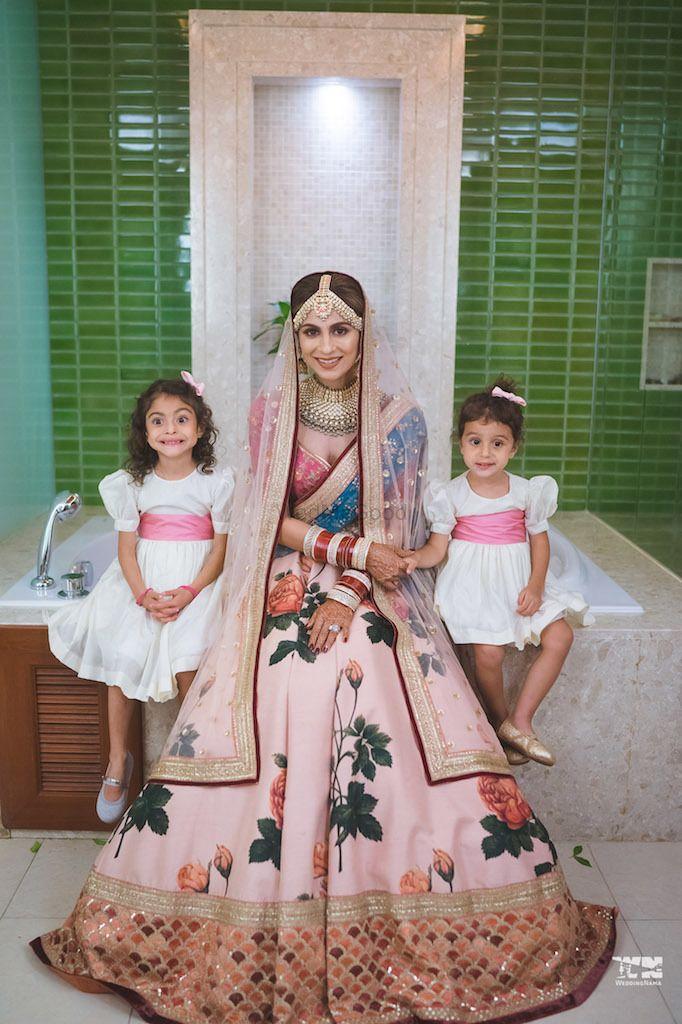 Photo of Bride wearing floral print sabya lehenga with flower girls
