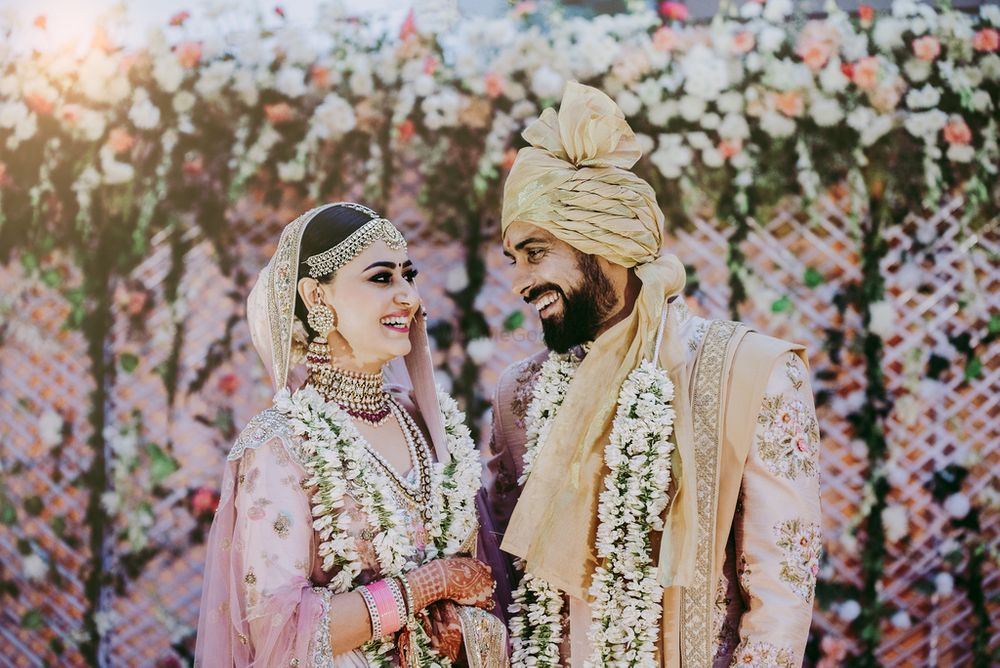 Photo of A bride and groom in coordinated outfits on their wedding day