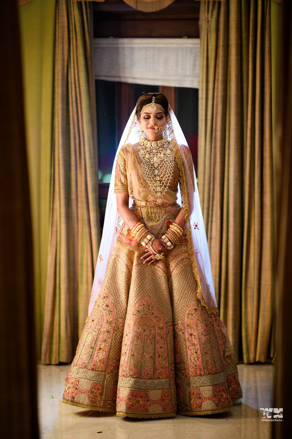 Photo of A bride in an embroidered lehenga and a heavy, layered bridal necklace