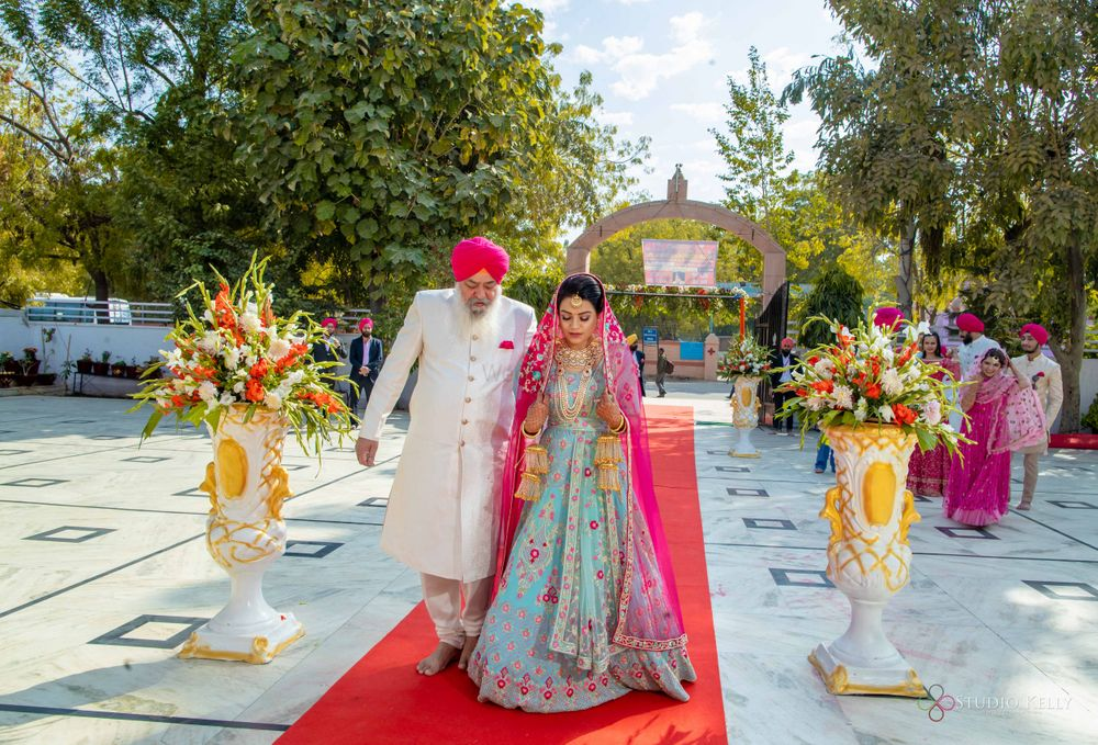 Photo of bridal entry idea for sikh bride with her father or grandfather