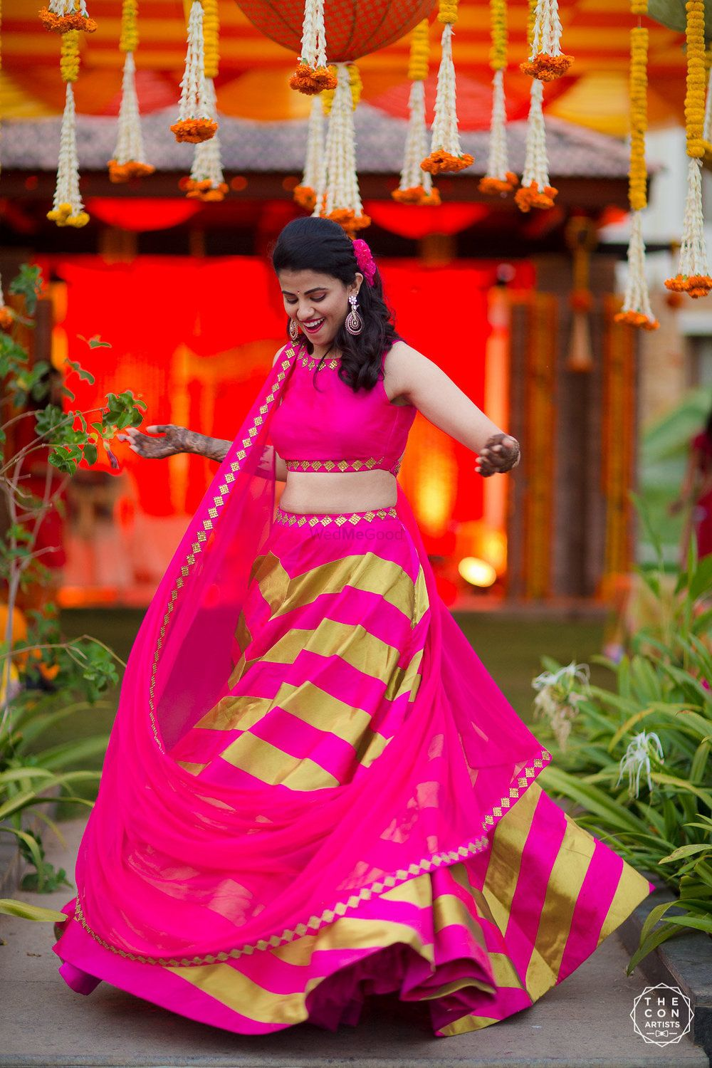 Photo of Bride twirling on mehendi in bright pink and lime green lehenga