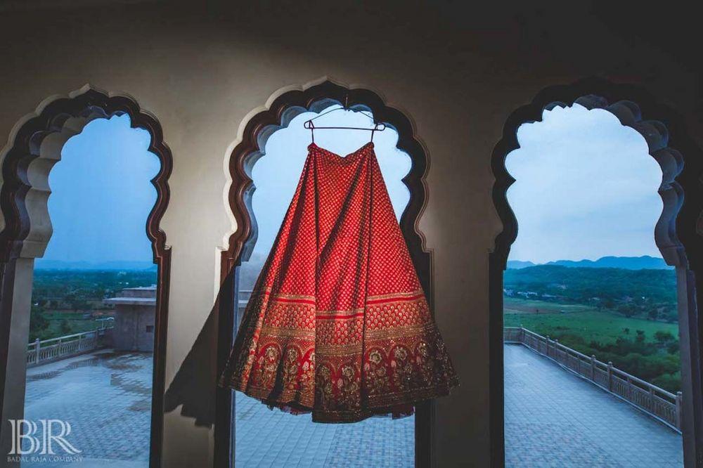 Photo of Bridal red sabysachi lehenga on hanger sunset shot