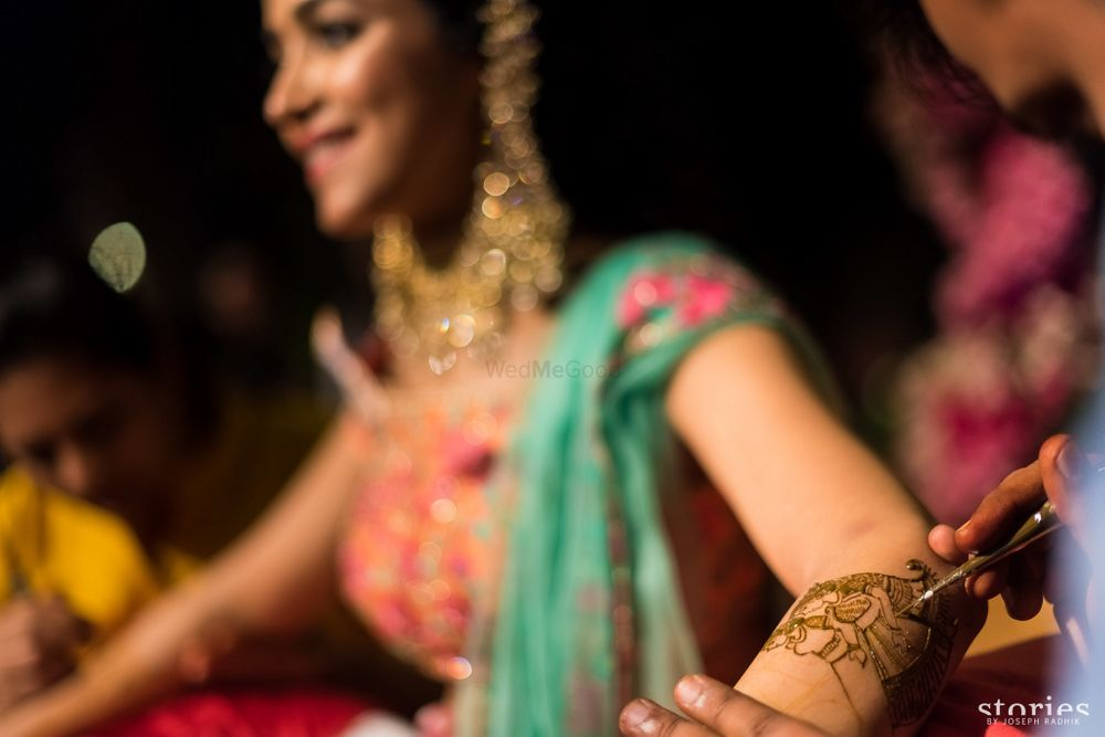 Photo of Bride getting mehendi put on arms