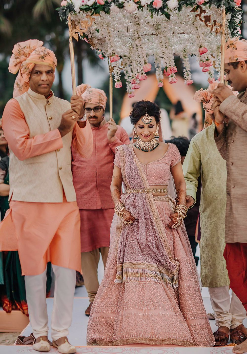 Photo of A bride in pink entering under a phoolon ki chaadar with her brothers