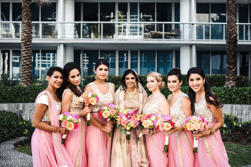 Photo of Bride with bridesmaids holding bouquets
