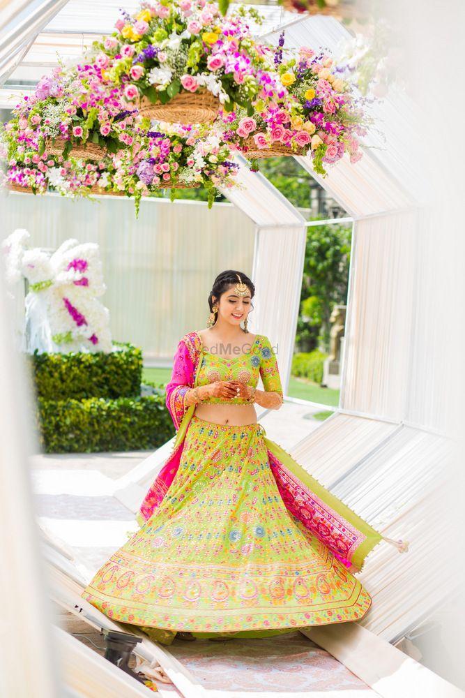 Photo of Bride in lime green and pink lehenga on mehendi