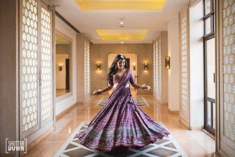 Photo of Twirling bride portrait in purple lehenga