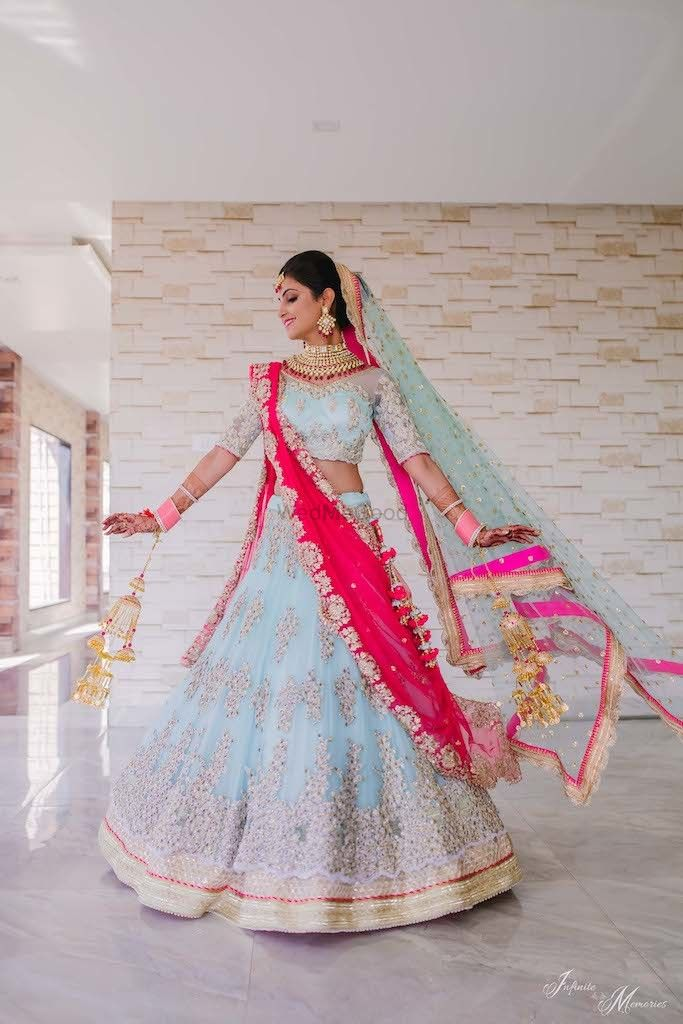 Photo of Twirling shot of a bride in powder blue lehenga.