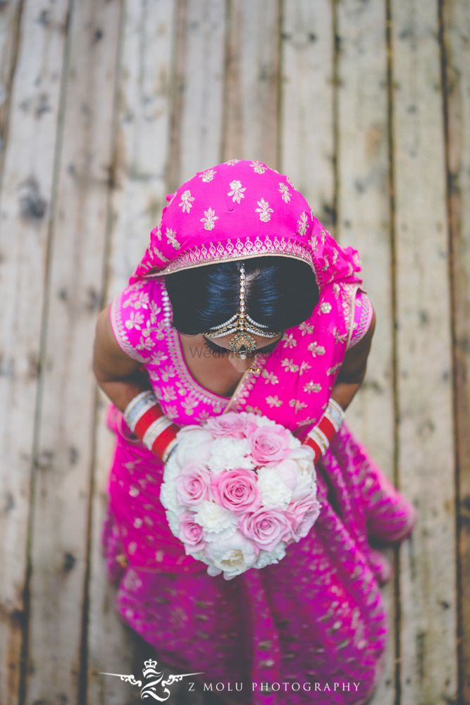Photo of Bride in bright pink lehenga holding bridal bouquet
