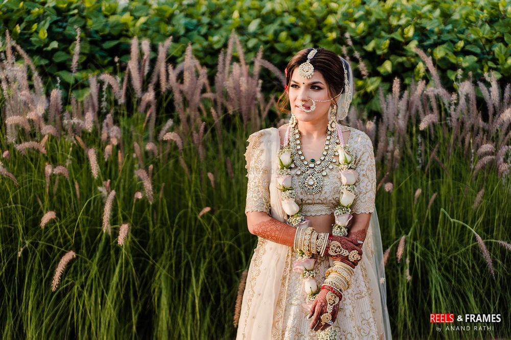 Photo of A bride in an ivory and gold lehenga with pastel jaimala