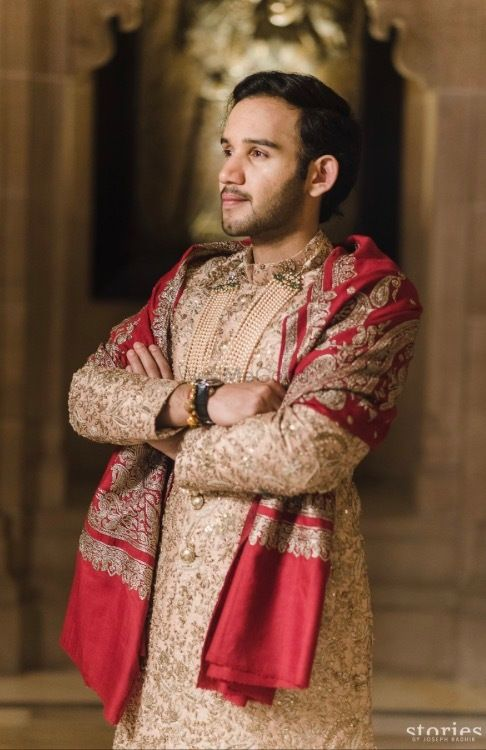 Photo of Groom sherwani in beige with red shawl