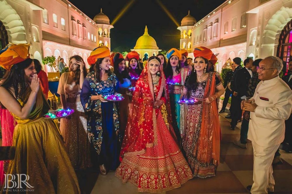 Photo of Bride entering with bridesmaids holding LED thalis