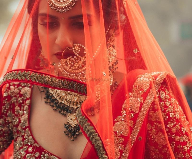 Photo of Bridal portrait with bride in oversized Nath and veil