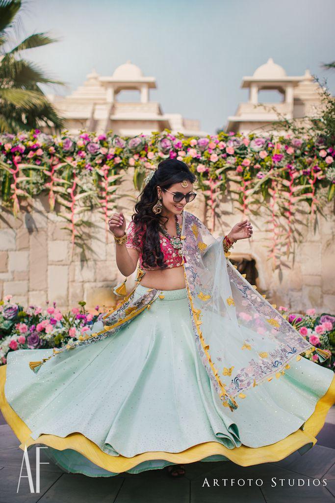 Photo of Bride twirling in blue mehendi lehenga