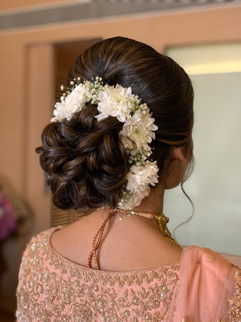 Photo of A twisted bridal bun outlined with white flowers.
