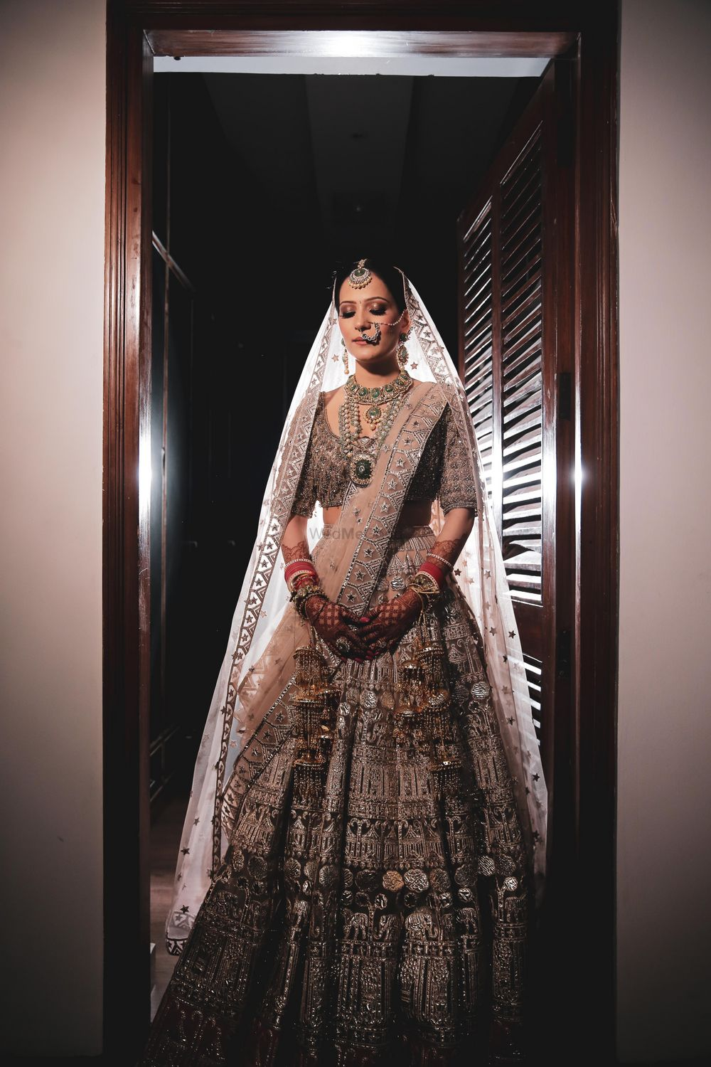 Photo of Bride in a pastel lehenga with silver detailing.