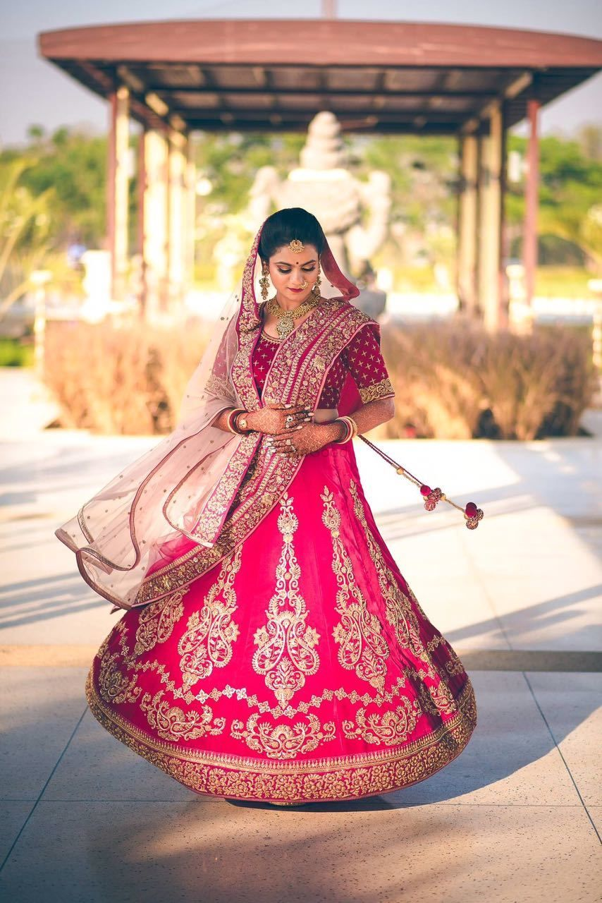 Photo of Bride twirling in red bridal lehenga thats light