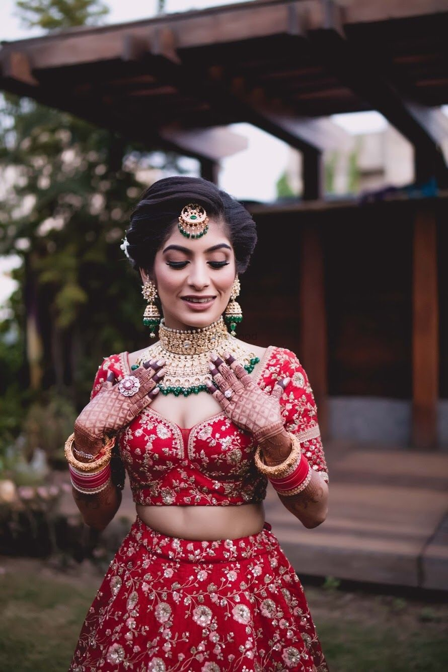 Photo of Bride in red blouse and green jewellery
