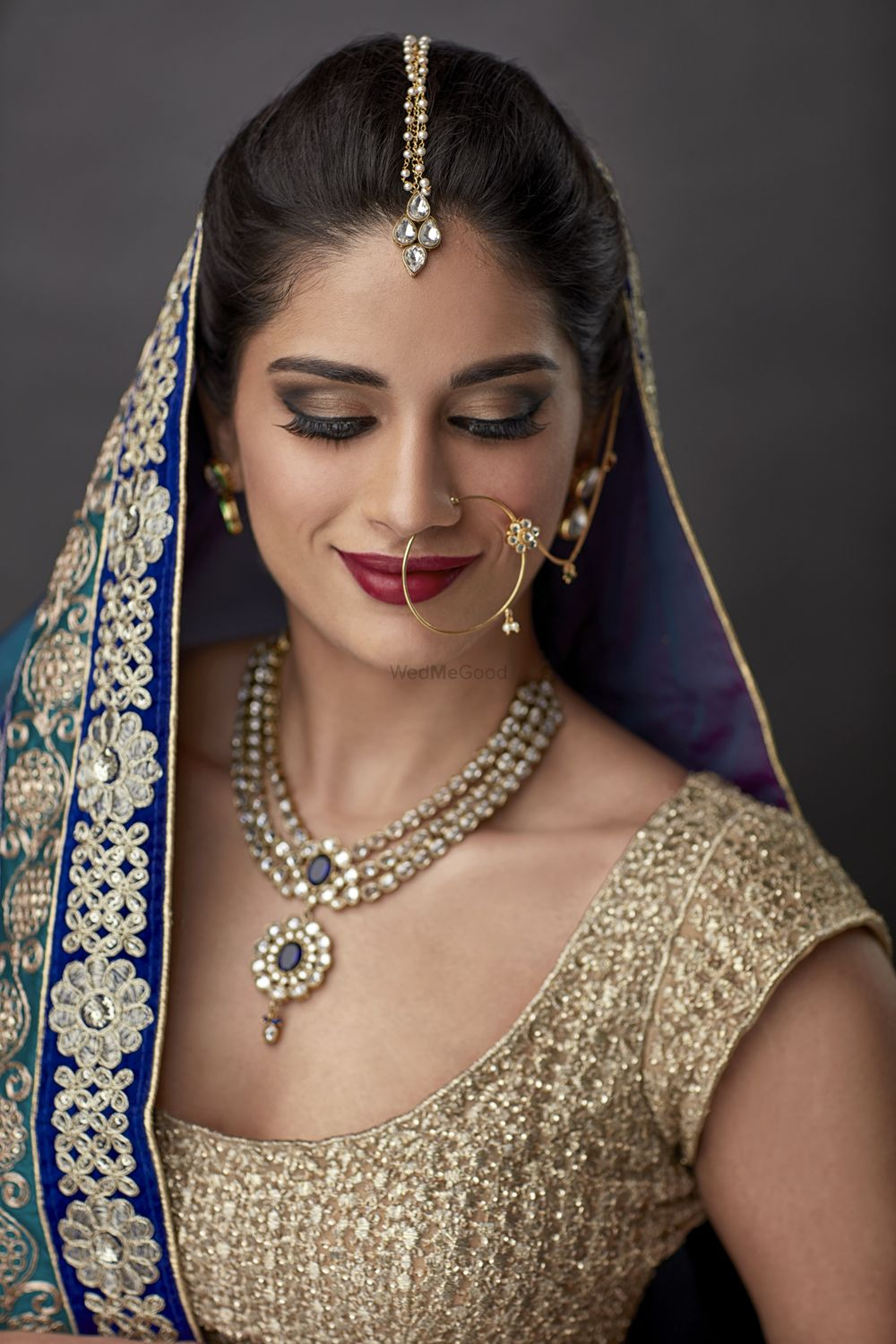 Photo of Emerald and diamond necklace with blue and gold lehenga