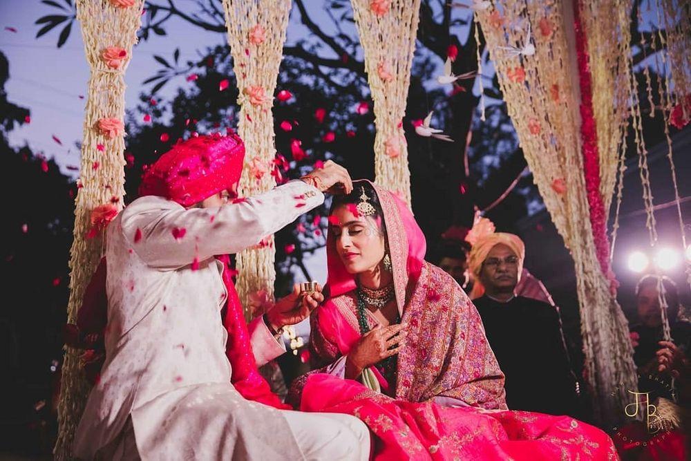 Photo of Groom applying sindoor on the bride.