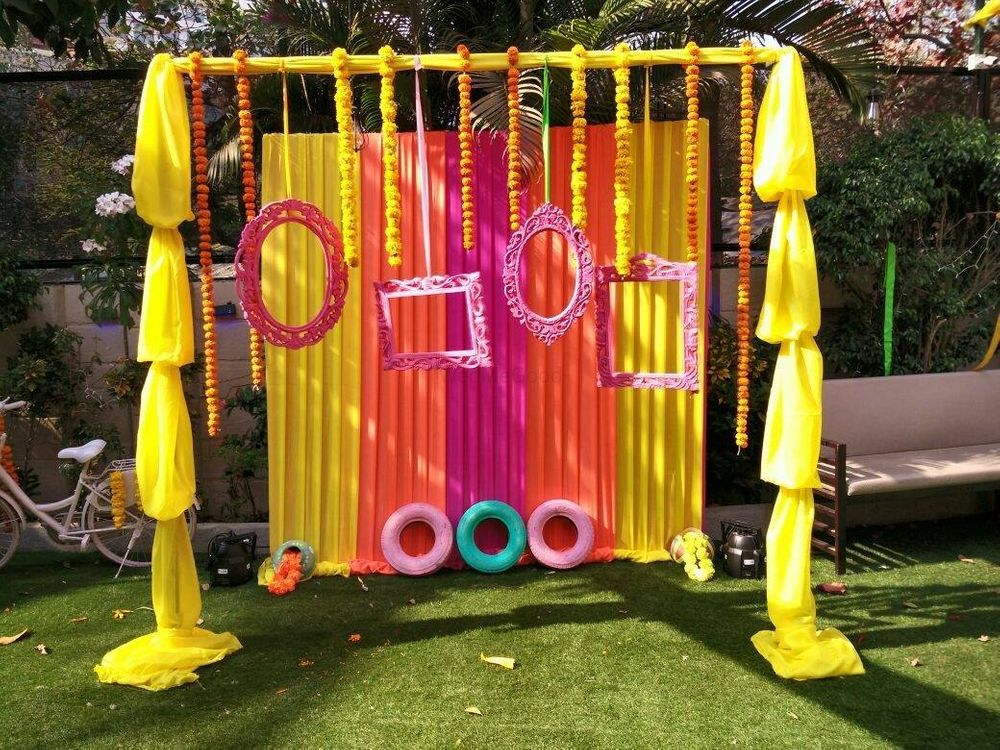 Photo of Photobooth made of colourful drapes, wooden frames and painted tyres.