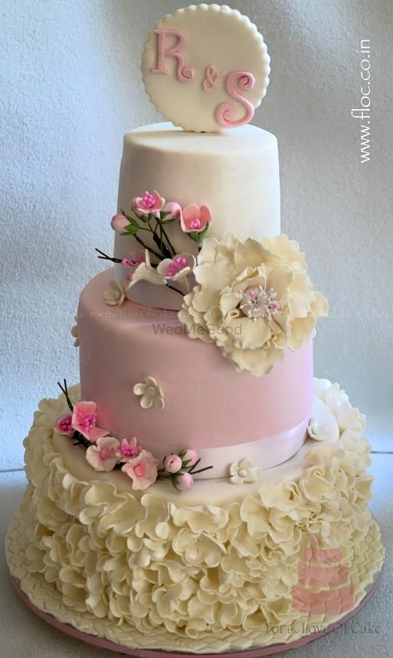 Photo of three tier pastel cake with flower detailing and cherry blossom