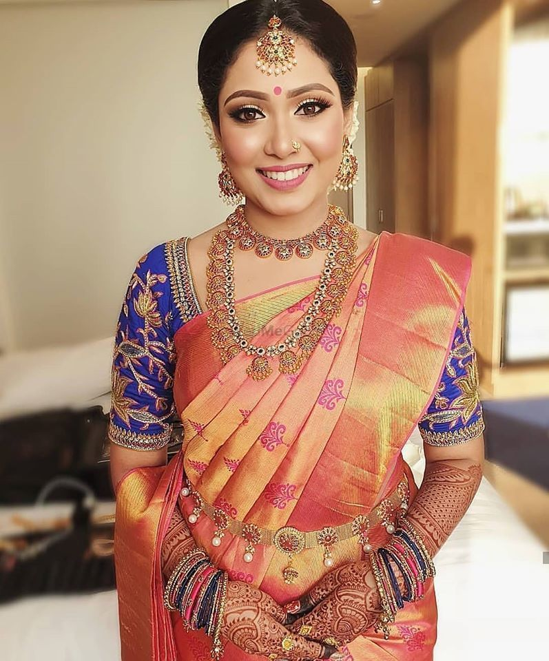 Photo of Southi Indian bride dressed in a coral saree with a navy blue blouse.